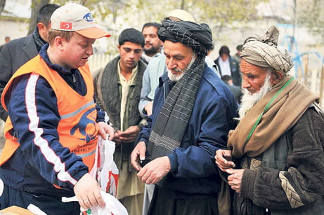 A Kimse Yok Mu relief worker delivers supplies to two elderly Afghanmen