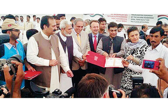 Turkish charity Kimse Yok Mu Director İsmail Cingöz and a board member present Pakistani officials with a land deed to the İkbaliye village. (Photo: Today's Zaman)