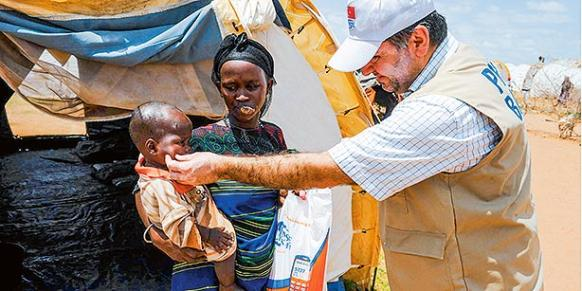 A Kimse Yok Mu volunteer hands out sacrificial meat to Somali refugees taking shelter in a Kenyan refugee camp on Eid al-Adha. (Photo: Sunday's Zaman)
