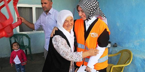A woman in the village of Bilge in Mardin province greets a Kimse Yok Mu volunteer (R) during an aid mission on Oct. 5. (Photo: Cihan)