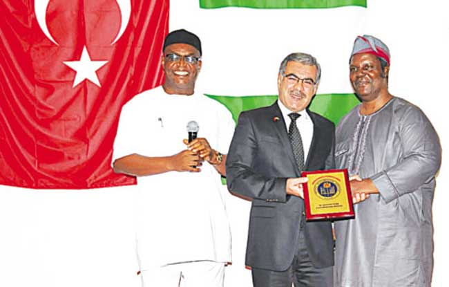 Chief Executive Officer, National Mathematical Centre (NMC), Prof Adewale Solarin (right), Group Managing Director, Nigeria Turkish International Colleges (NTIC), Mehmet Basturk and Chairman of Governing Council of West African Examinations Council, Daniel Uwazurike, during the presentation of NMC 2014 Awards to Basturk at the Sheraton Hotels, Abuja