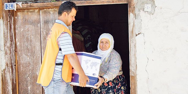 A member of Turkish charity association Kimse Yok Mu is seen giving a relief supply kit to a local in this file photo.(Photo: Cihan)