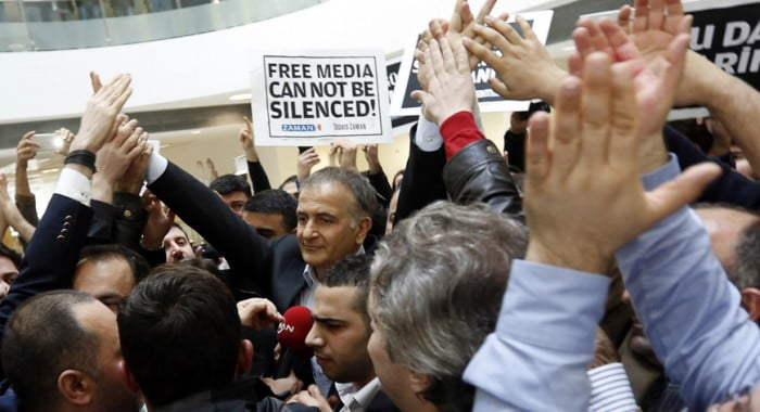 Zaman editor-in-chief Ekrem Dumanli (C), escorted by plainclothes police officers, is cheered by his colleagues as he leaves the headquarters of Zaman daily newspaper in Istanbul, Dec. 14, 2014. (photo by REUTERS/Murad Sezer)