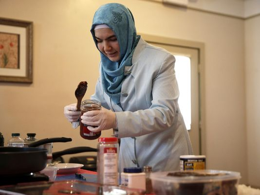Esra Akbas demonstrates how to fill a stuffed eggplant, or Karniyarik, during a Turkish cooking class at the Istanbul Cultural Center on Sunday. (Photo: Joe Rondone/Democrat)