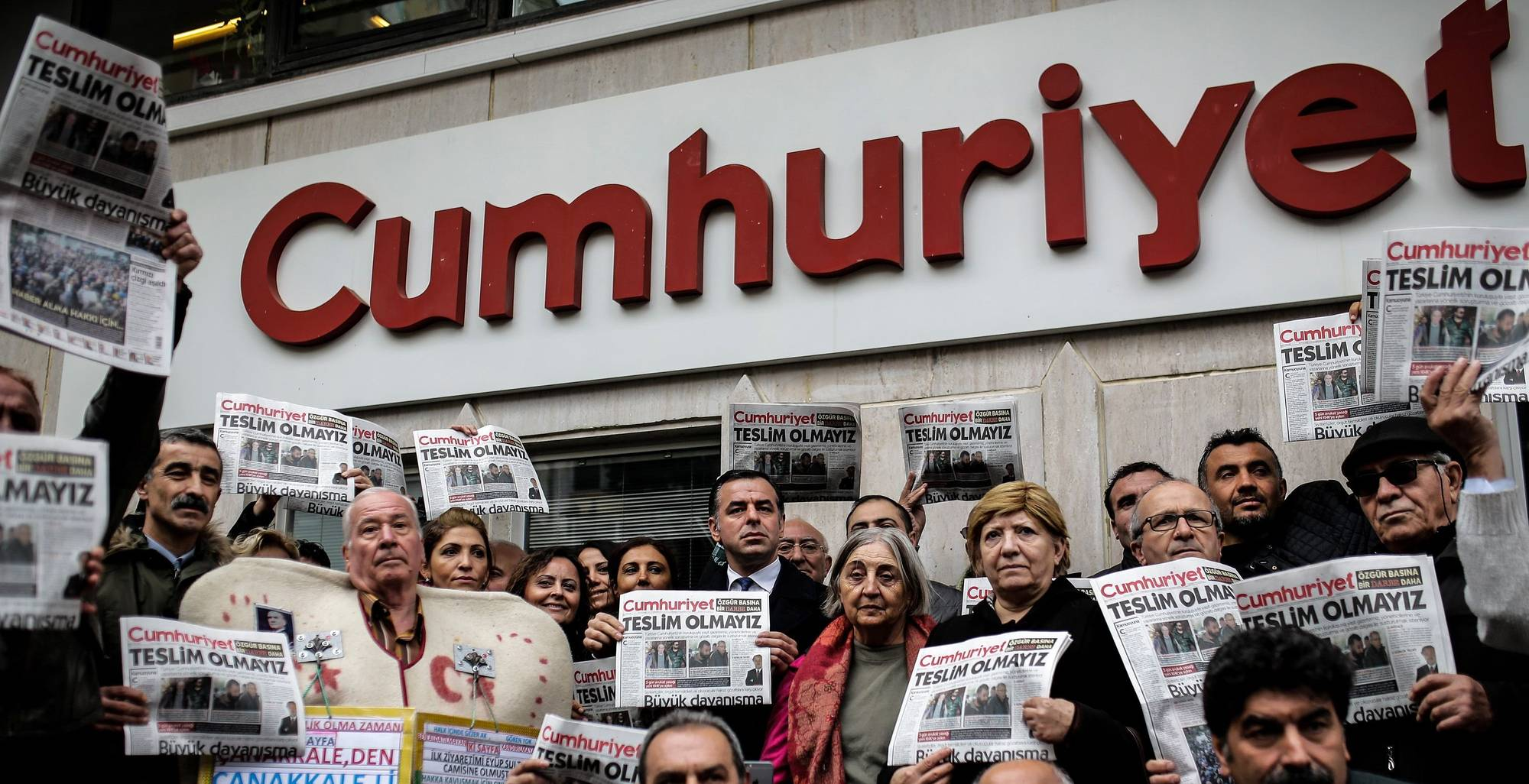 Protesters hold copies of the latest edition of the Turkish daily newspaper