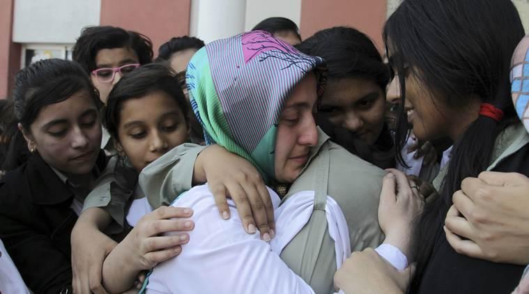 Pakistani students of the Pak-Turk International school comfort their Turkish teacher in Lahore, Pakistan, Nov. 17, 2016. (AP Photo/K.M. Chaudhry)