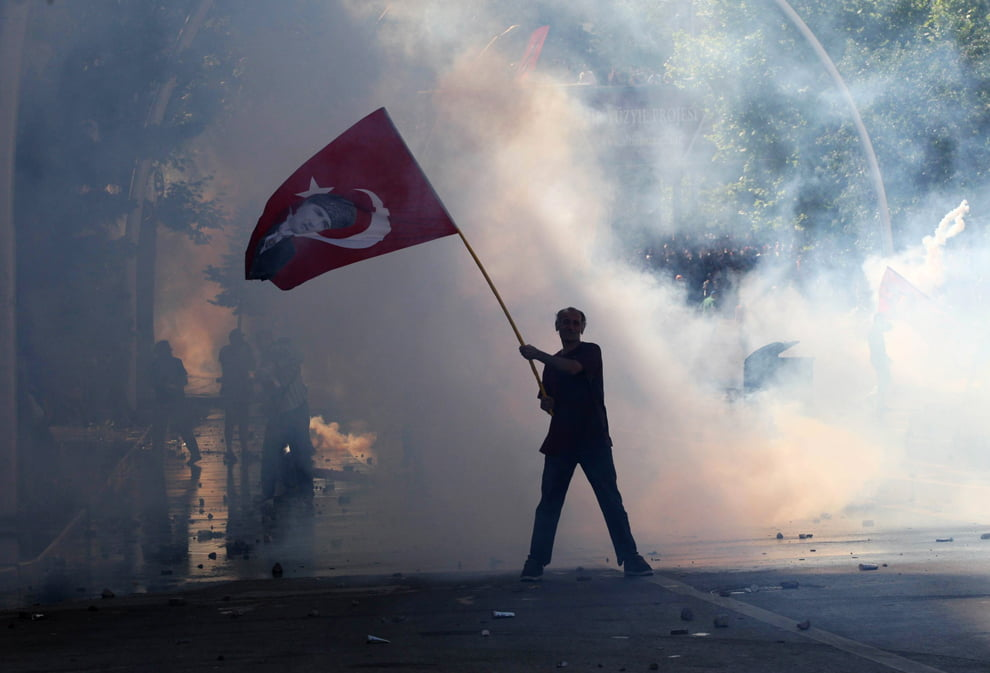 Tear gas surrounds a protestor holding a Turkish flag with a portrait of the founder of modern Turkey, Mustafa Kemal Ataturk, as he takes part in protests against the Turkish Prime Minister and his ruling Justice and Development Party (AKP) in Ankara on June 1, 2013. (Adem Altan/AFP/Getty Images)