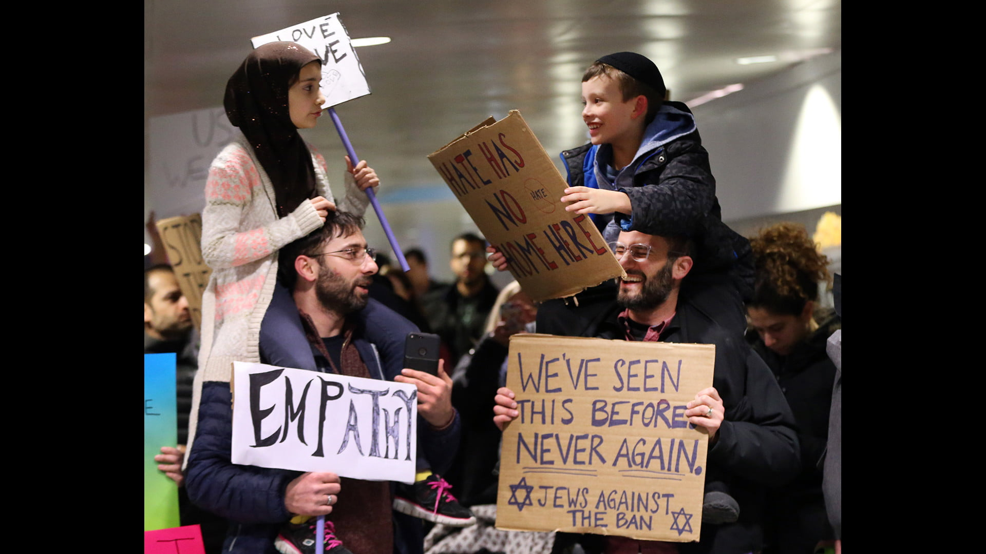 Meryem Yildirim, 7, left, sitting on the shoulders of her father, Fatih, of Schaumburg, and Adin Bendat-Appell, 9, sitting on the shoulders of his father, Rabbi Jordan Bendat-Apell, of Deerfield, protest President Donald Trump's immigration and refugee order at O'Hare International Airport on Jan 30, 2017. (Nuccio DiNuzzo / Chicago Tribune)