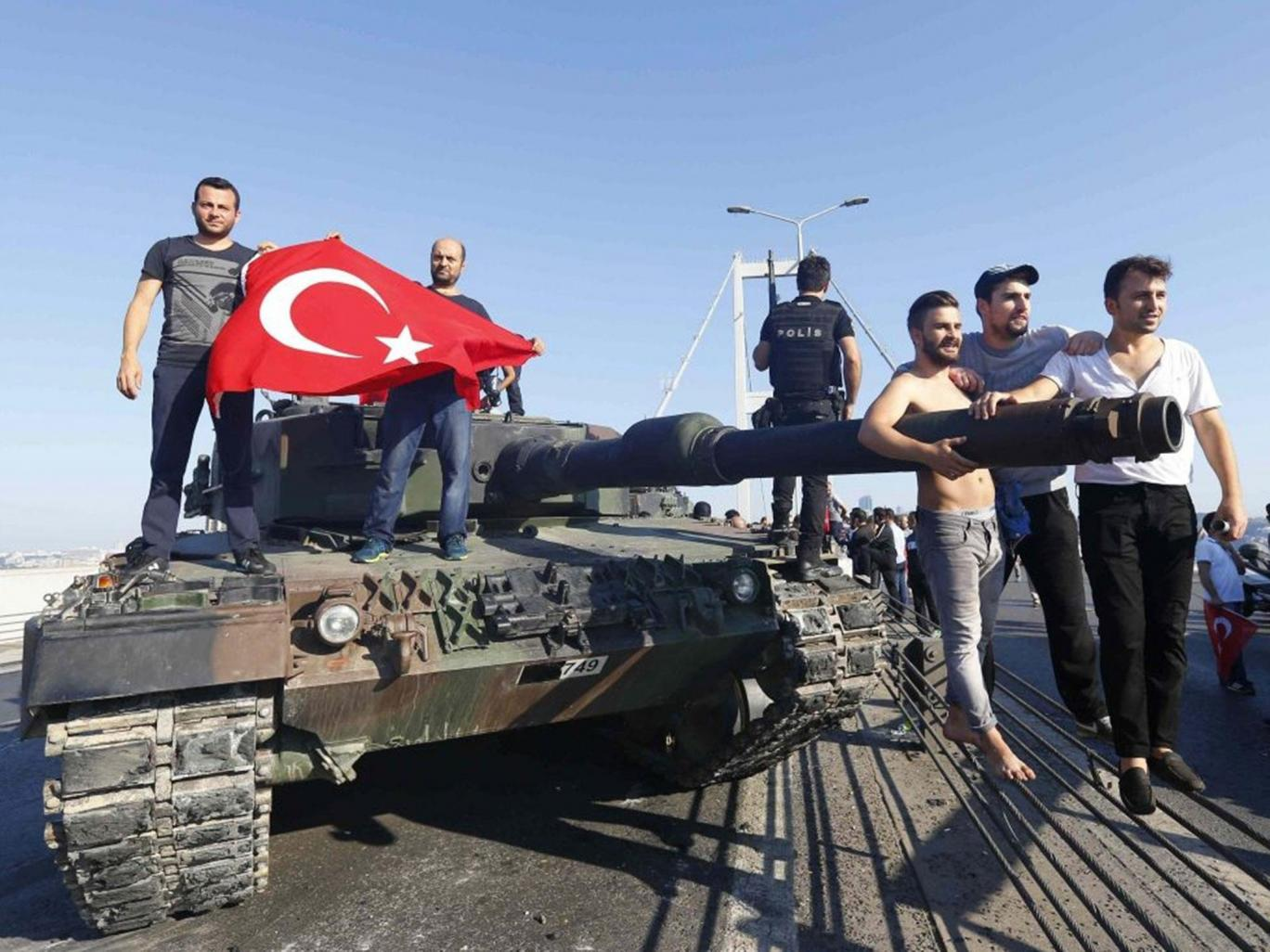 Civilians carry the Turkish flag onto a tank abandoned by rebel soldiers Reuters