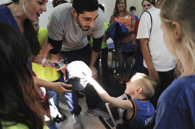 Kyle Phillips / The Transcript.  Oklahoma City Thunder's Enes Kanter gives Henry Hale a hat earlier this year during his visit at the J.D. McCarty Center. Kanter, an outspoken critic of the current Turkish government, has been facing increasing pressure from Turkey to stop talking. His passport has been canceled, a warrant for his arrest has been issued, and his father was arrested this morning.