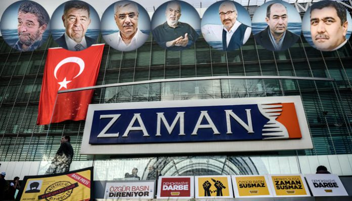 The logo of Turkish daily newspaper Zaman is seen on the headquarters building as people demonstrate in support of the newspaper in Istanbul on March 4, 2016. An Istanbul court on Friday ordered into administration the Turkish daily newspaper Zaman that is sharply critical of President Recep Tayyip Erdogan, amid growing alarm over freedom of expression in the country.