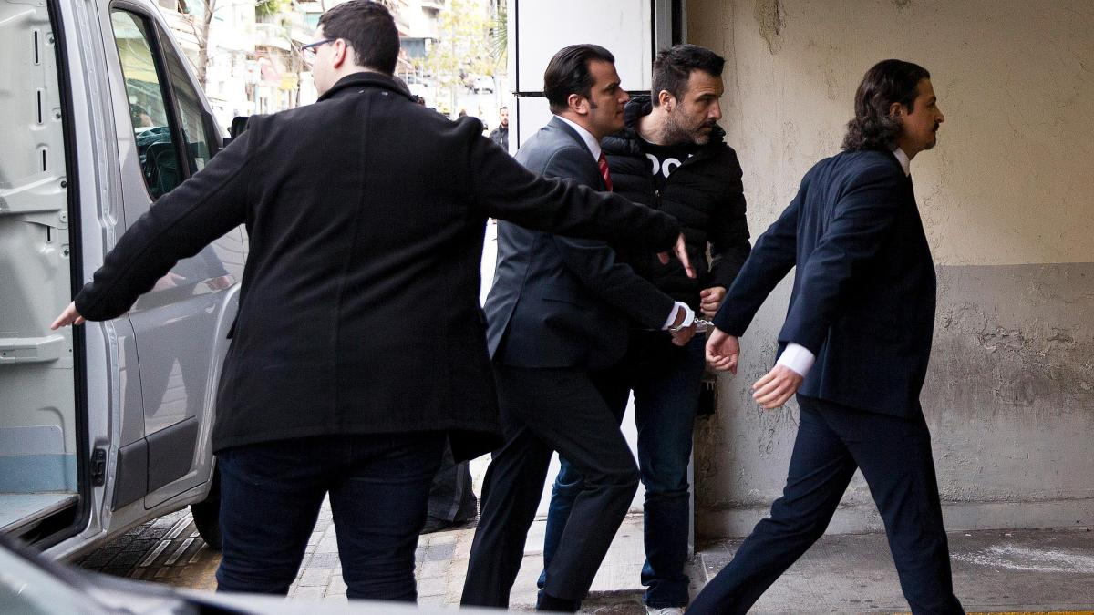 Two Turkish servicemen being taken in handcuffs to the Athens appeals court this morning. The court refused Turkey's request to extradite them.  PETROS GIANNAKOURIS/AP